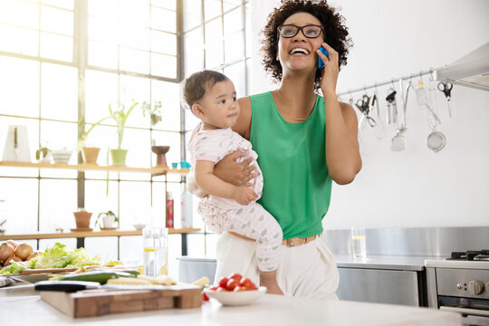 Mother holding her baby daughter while using mobile phone in kitchen