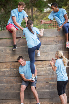 Teammates helping woman over wall on boot camp obstacle course