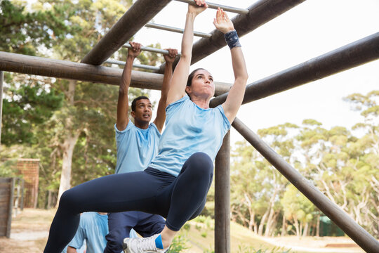 Determined woman swinging on monkey bars on boot camp obstacle course