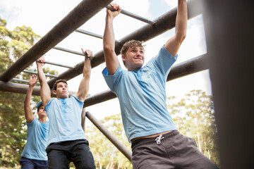 Keuken foto achterwand Aap Determined men crossing monkey bars on boot camp obstacle course