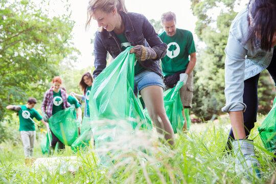 Environmentalist volunteers picking up trash in field