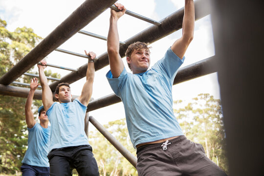 Determined men crossing monkey bars on boot camp obstacle course