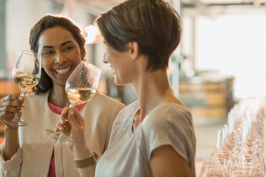 Smiling women wine tasting white wine in winery tasting room