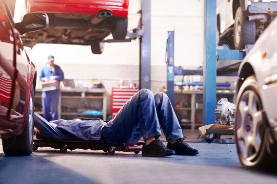 Mechanic under car in auto repair shop