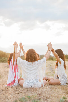 Boho women sitting in circle with arms raised connected in rural field