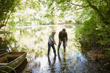 Father and son fishing with nets in forest pond