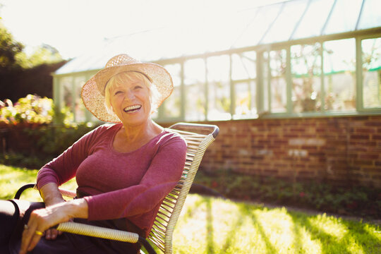 Portrait enthusiastic senior woman sitting outside sunny greenhouse