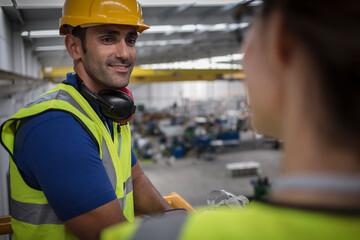 Smiling male supervisor talking to coworker on platform in factory Fotobehang