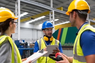 Supervisor and workers with clipboard and digital tablet talking in factory Wall mural