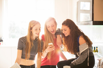 Teenage girls texting with cell phone in sunny kitchen