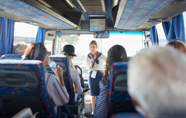 Female tour guide with microphone talking to active senior tourists on tour bus