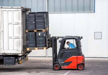 Unloading cargo from the truck  .  Loader operating forklift at warehouse