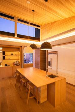 Illuminated slanted wood ceiling and pendant lights over kitchen island
