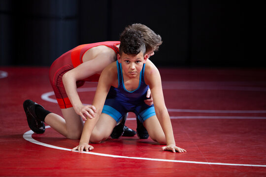 Wrestlers in red and blue singlets practicing on a red mat.