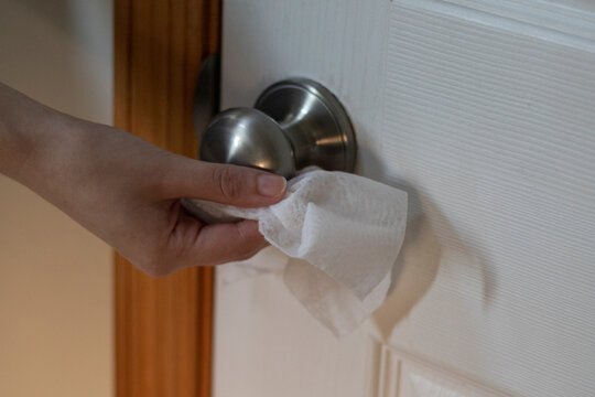 Close up of a woman disinfecting a door knob or door Handle because of the Novel Coronavirus or Corona virus Disease (Covid-19). Antiseptic, Hygiene and Health care.