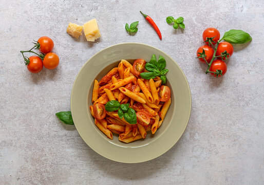 Penne pasta in arrabbiata sauce with tomatoes, red chili peppers, garlic, basil, and cheese.