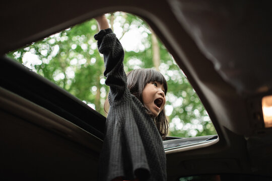 little girl stood screaming with her hands up through the open roof of the car