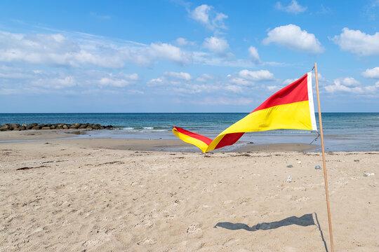 Multi-colored flag on a sandy beach. Denmark. North Sea. Seascape.