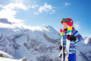 Portrait of smiling cute girl in pink helmet and color ski, goggles off over high mountain peaks profile view