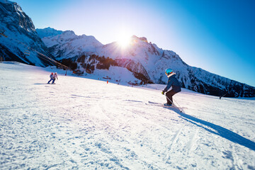 Group of kids ski down before sunset on Alpine mountain slope