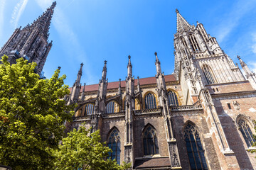 Fototapete - Ulm Minster or Cathedral of Ulm city, Germany. It is top landmark of Ulm. Ornate facade of old Gothic church against sky in summer.
