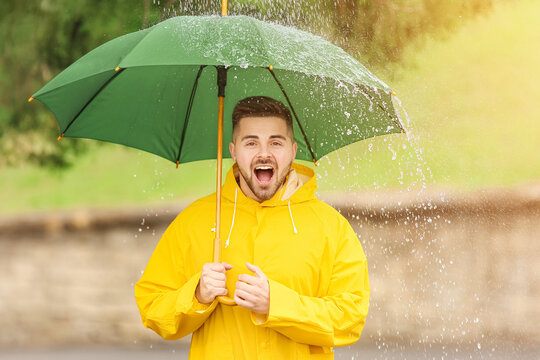 Young man with umbrella wearing raincoat outdoors