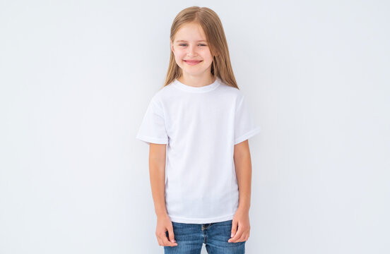 Cute little kid girl wearing a blank white t-shirt, on white background