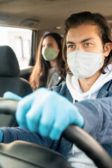 Serious young man in cloth mask and gloves driving taxi client during coronavirus