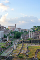 Perspective of the Roman Forum ancient ruins and Colosseum ampitheater, in Rome, Italy, with temple of Saturn, temple of Vesta, Basilica of Maxentius, Arch of Titus and Palatine Hill at sunrise