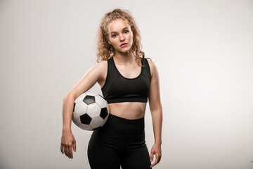 Pretty young female soccer player with long blond curly hair holding ball