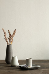Two white ceramic vases standing on wooden table on background of black one