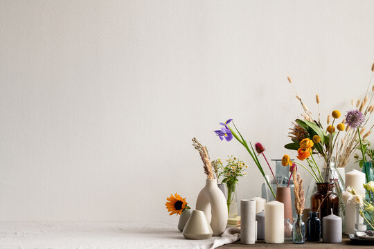 Large group of various handmade ceramic, clay and glass vases with flowers