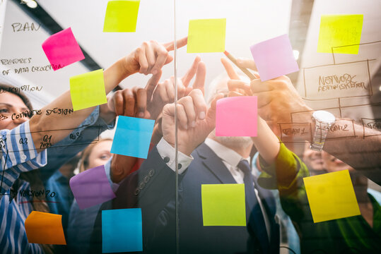 Team of people at work in the office indicates with their hand a post-it on the glass