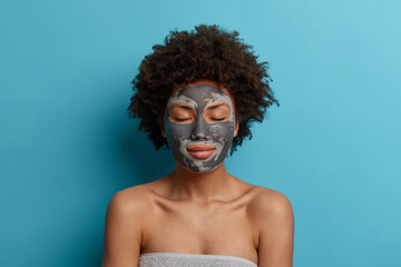 Beautiful young woman has clean fresh skin, wears beauty clay mask on face, stands with closed...