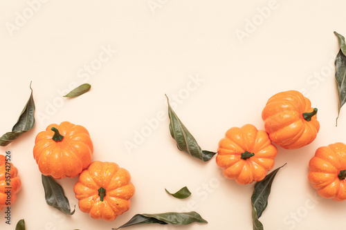 Autumn Minimal composition. Autumn, fall, thanksgiving day, halloween concept. Yellow background with pumpkins. Top view, flat lay