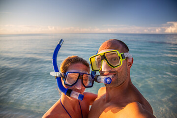 Young couple taking selfie in tropical scene with waterproof camera. Boat trip snorkeling excursion at Maldives islands. Travel lifestyle and holiday concept, summer vibes, funny couple image