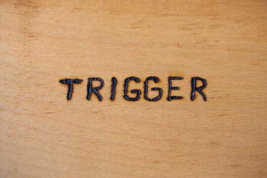 the word trigger handwritten on flat bare plywood surface with woodburner