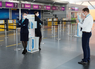 An employee takes a picture of his colleagues at a check-in area at the Boryspil International Airport outside Kiev