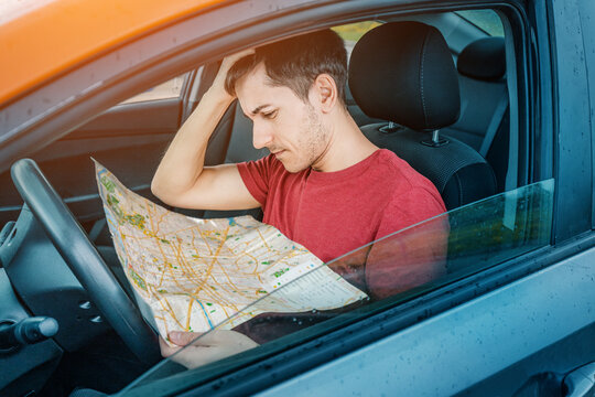 A frustrated man gets lost and tries to find his location on a map while sitting in a car