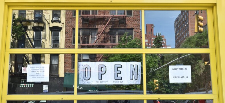 Open sign in the window of a small business with yellow frame and brick buildings in the reflection, June 10, 2020, in New York.