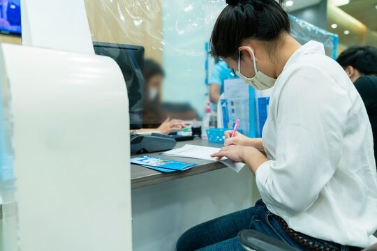 New normal asian female sit and write paper work at commercial bank with face mask and social distancing new lifestyle after covid 19 spread epidemic