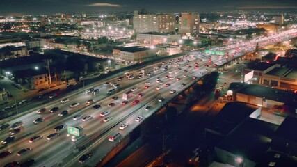 Fotobehang - Busy traffic on I-10 freeway in downtown Los Angeles at night. Aerial city skyline panorama view. 4K UHD.