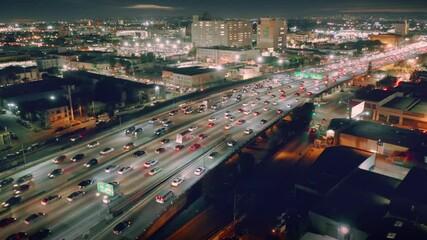 Klistermärke - Busy traffic on I-10 freeway in downtown Los Angeles at night. Aerial city skyline panorama view. 4K UHD.
