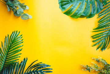 Tropical palm leaves on yellow background. Flat lay, top view