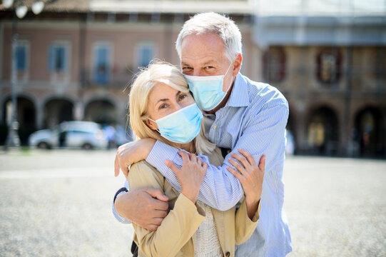 Love in the time of Coronavirus. Senior couple hugging outdoor wearing masks