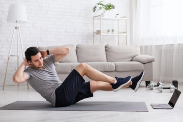 Sport and healthy lifestyle. Man does exercises for abdominal muscles and watches online training