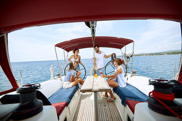Happy friends  drinking on a yacht. Friends on vacation and luxury travel.