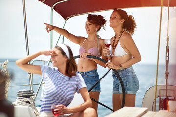 Girls drinking on a yacht and enjoying at vacation and luxury travel.