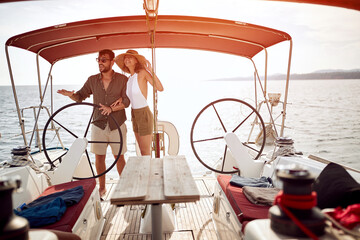 Young couple standing on the luxury yacht and enjoying