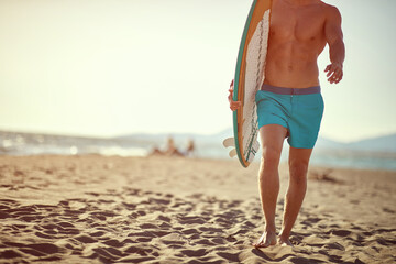 Man surfers on a beach. Portrait of  men holding a surfboard